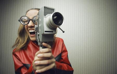 Nerdy vrouw met behulp van ouderwetse filmcamera
