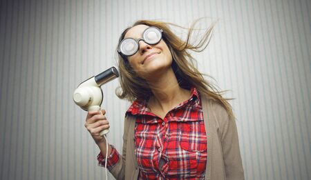 Nerdy woman using hair drayer on vintage wallpaper photo