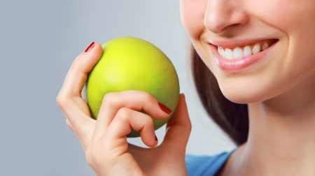 smile close up: Young woman holding a green apple, close up