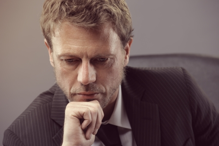 Close up portrait of a mature businessman looking down worried photo