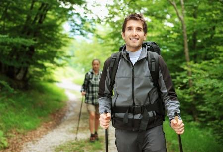 walking pole: Young couple enjoying a nordic walk, man is smiling