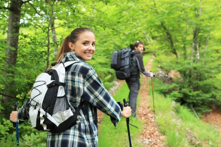 walking pole: Young couple enjoying nordic walking in a forest Stock Photo