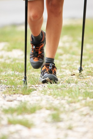 walking pole: Woman hiking and nordic walking in forest. Sport shoe close up