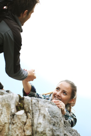 recreational climbing: Female climber need a help to reach the top of the mountain