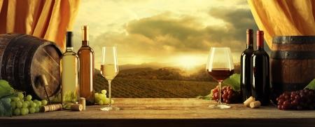 Botellas de vino, barriles y viñedo en puesta del sol Foto de archivo