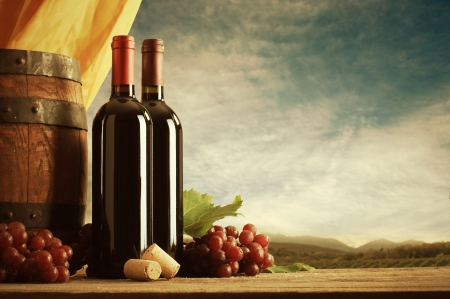 Red wine bottles with barrel and grapes, vineyard on background photo