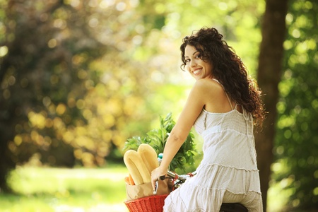 Portrait of a smiling young woman riding bicycle with groceries in basket photo