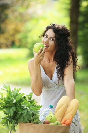 Cheerful young woman eating a green apple photo