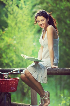 Young cheerful woman reading a book at a park Stock Photo - 21512547