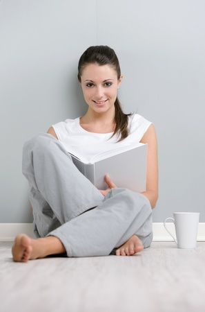 Portrait of young woman with book and a cup of coffee sitting on floor photo