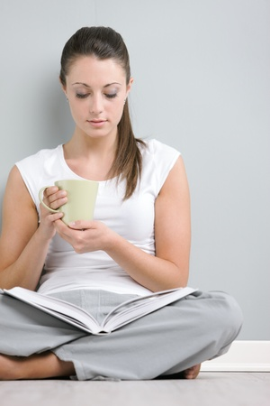 Portrait of young woman with book holding a cup of coffee or tea photo