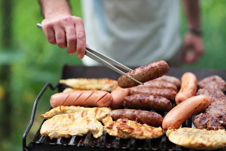 Grilling at summer weekend. Fresh meat preparing on grill.Shallow deep of field Stock Photo