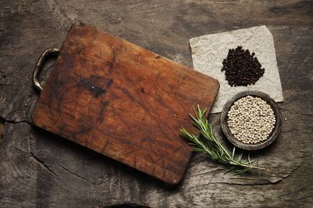 Cutting Board, rosemary and spices on a old wooden table photo