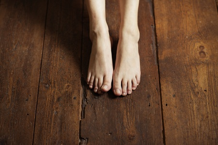 Cropped image of female bare feet on a wooden floor photo
