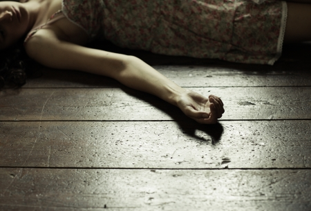dead woman: Cropped image of a woman lying on the floor Stock Photo