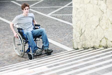persona en silla de ruedas: Un joven en una silla de ruedas que no pueden subir las escaleras