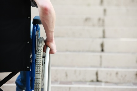 unaccessible: Wheelchair user in front of staircase Barrier