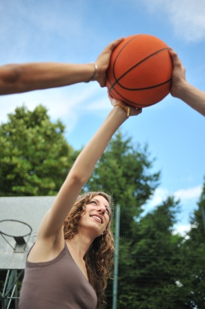 Friendship & sport. Three teenagers holding a basket ball Stock Photo