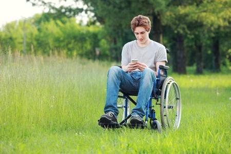 persona en silla de ruedas: Hombre discapacitado joven que env�a un mensaje por tel�fono en el parque