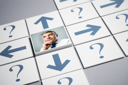 Senior businessman thinking surrounded by question marks and arrows photo