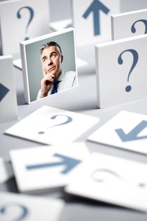 Portrait of a confused businessman surrounded by question marks and arrows photo