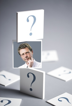 possibility: Portrait of a confused businessman surrounded by question marks