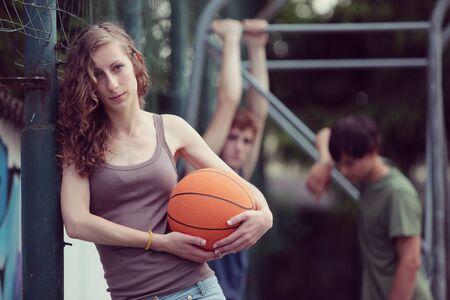 baloncesto chica: Chica adolescente con el baloncesto, sus amigos en el fondo