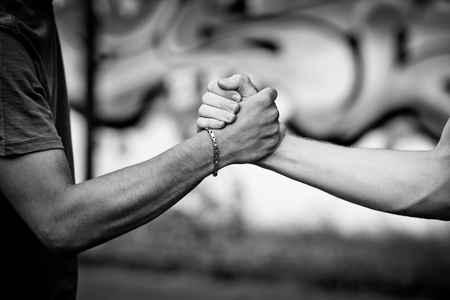 urban youth: White teen and Black teen clasp hands against a wall with graffiti