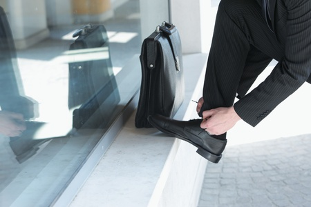 mens shoes: A businessman  wearing a suit is tying his shoes