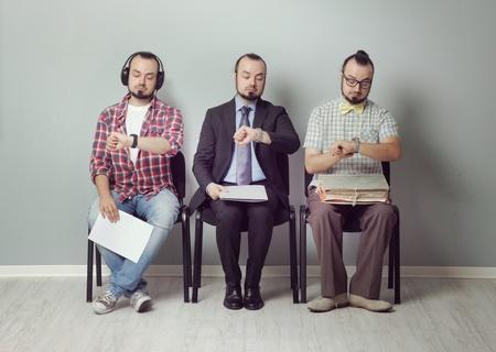 interview job: Imagen conceptual de tres hombres esperando para una entrevista Foto de archivo