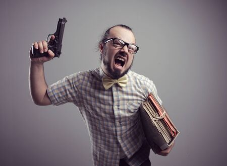 crazy man: Office worker shouting with a gun on grey background