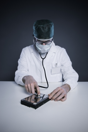 Doctor or Technician wearing a lab coat and stethoscope examining an hard disk photo