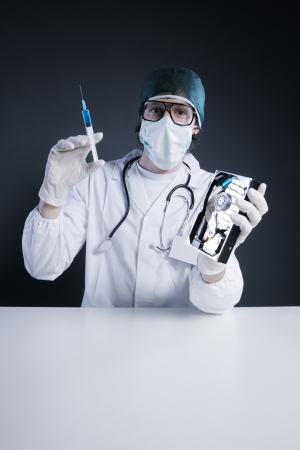 Computer virus concept. Technical  Doctor with syringe and hard disk photo