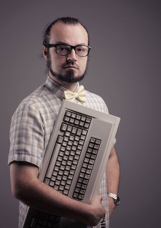Funny guy posing with a keyboard on grey background photo