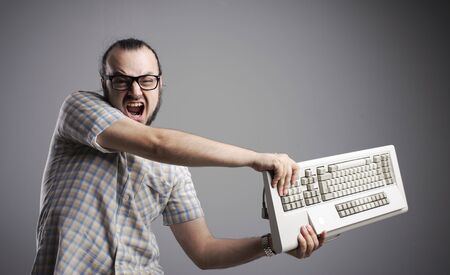 and the horizontal man: Angry man is destroying a keyboard Stock Photo