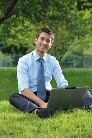 surfing the internet: Smiling businessman working on laptop outdoors Stock Photo