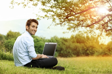 Businessman sitting on the grass is working on laptop Stock Photo