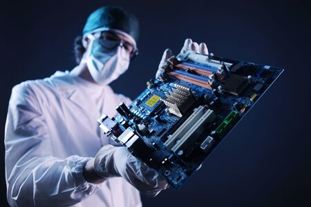 determines: Computer engineer determines the main board problem. Stock Photo
