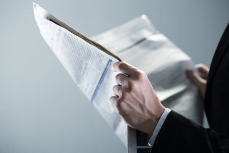 Businessman reading a newspaper, hand close up photo