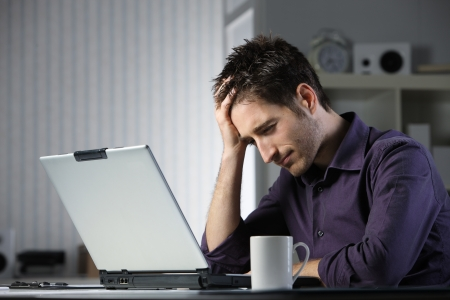 overwork: Unhappy stressed male student looking at his laptop computer with his head in his hands