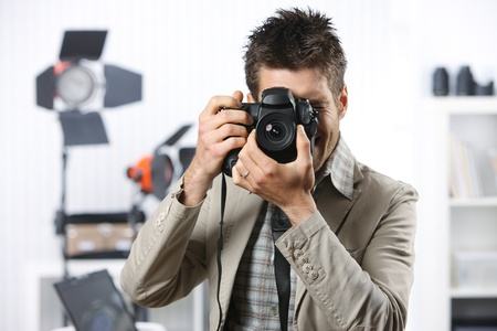 Young man taking photo with professional digital camera photo