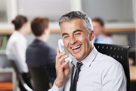 Mature businessman at the phone with colleagues in the background photo