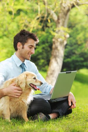 Young business man and his dog working outdoors with laptop on the grass photo