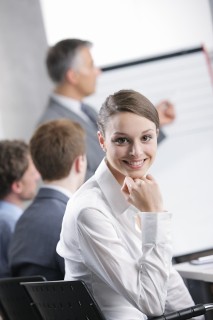 Smiling woman sitting at a business meeting with colleagues photo