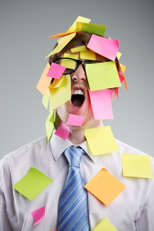 Office worker with post-its all over his face photo