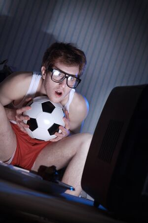 Young man soccer fanatic getting really into the soccer game on television photo