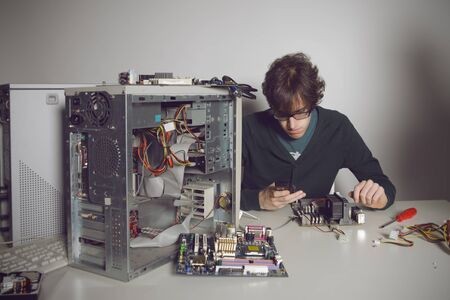 Computer Repair: young man using cellphone photo