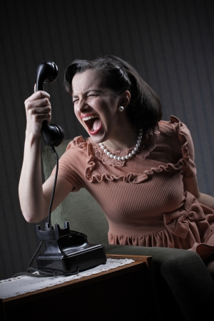 woman screaming: Angry woman screaming at retro phone, 1950 style