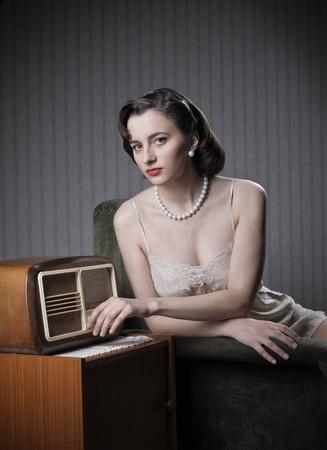 Sensual woman wearing lingerie listening music on old radio photo