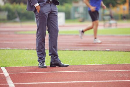 mens shoes: Businessman standing on running track, an athlete is running in the background